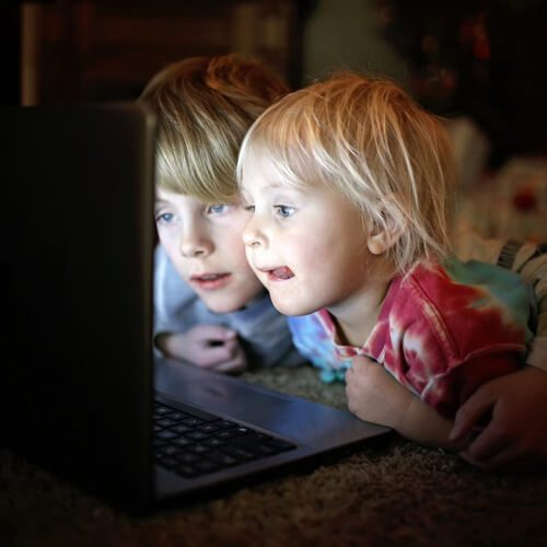 Two children staring into a laptop screen